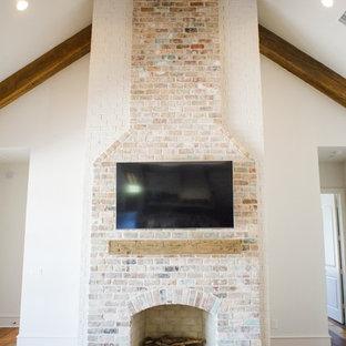 Großes, Offenes Klassisches Wohnzimmer mit weißer Wandfarbe, braunem Holzboden, Kamin, Kaminumrandung aus Backstein, Wand-TV und braunem Boden in Houston
