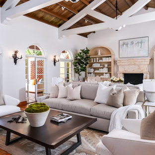 Inspiration for a mediterranean terra-cotta floor and orange floor family room remodel in Miami with white walls, a standard fireplace and a stone fireplace