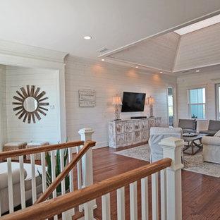 Inspiration för ett mellanstort lantligt allrum med öppen planlösning, med en hemmabar, vita väggar, mellanmörkt trägolv, en väggmonterad TV och brunt golv