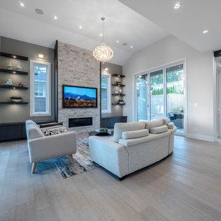 バンクーバーの大きいコンテンポラリースタイルのおしゃれなファミリールーム (グレーの壁、淡色無垢フローリング、横長型暖炉、石材の暖炉まわり、壁掛け型テレビ、グレーの床) の写真