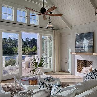 Cette photo montre une salle de séjour nature de taille moyenne et ouverte avec un mur blanc, un sol en bois clair, une cheminée standard, un manteau de cheminée en pierre, un téléviseur dissimulé et un sol beige.