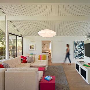 サンフランシスコのミッドセンチュリースタイルのファミリールームの画像 (白い壁、壁掛け型テレビ、淡色無垢フローリング)