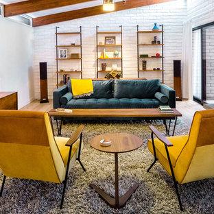 フェニックスの大きいミッドセンチュリースタイルのおしゃれな独立型ファミリールーム (白い壁、淡色無垢フローリング、標準型暖炉、レンガの暖炉まわり、茶色い床、壁掛け型テレビ) の写真
