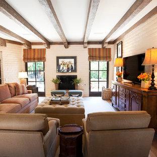 フェニックスの広いサンタフェスタイルのおしゃれなオープンリビング (ベージュの壁、テラコッタタイルの床、標準型暖炉、据え置き型テレビ、レンガの暖炉まわり、茶色い床) の写真