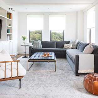 Small transitional enclosed dark wood floor and brown floor family room photo in New York with white walls and a media wall
