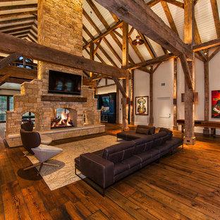 Imagen de sala de juegos en casa abierta, campestre, grande, con paredes blancas, suelo de madera en tonos medios, chimenea de doble cara, marco de chimenea de piedra, suelo marrón y televisor colgado en la pared