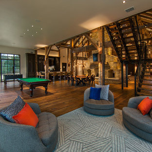 Game room - large rustic open concept medium tone wood floor and brown floor game room idea in Austin with white walls, a two-sided fireplace, a stone fireplace and a wall-mounted tv