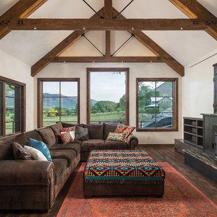 Modelo de sala de estar rústica con paredes blancas, suelo de madera oscura, estufa de leña, televisor retractable y suelo marrón
