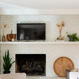 Kleines, Abgetrenntes Klassisches Wohnzimmer mit blauer Wandfarbe, braunem Holzboden, Kamin, Kaminumrandung aus Backstein, Wand-TV, braunem Boden, freigelegten Dachbalken und Wandpaneelen in Sonstige