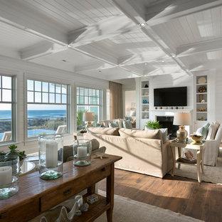 チャールストンの大きいビーチスタイルのおしゃれなファミリールーム (白い壁、無垢フローリング、標準型暖炉、金属の暖炉まわり、壁掛け型テレビ、茶色い床) の写真
