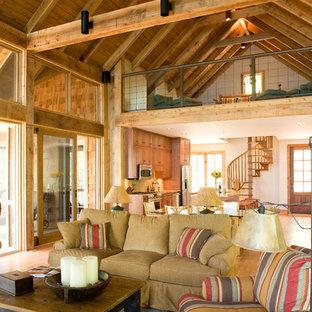 バーミングハムの大きいおしゃれなファミリールーム (淡色無垢フローリング、茶色い壁、標準型暖炉、石材の暖炉まわり、壁掛け型テレビ、茶色い床) の写真