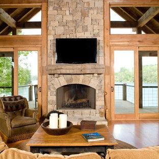 Cette image montre une grande salle de séjour craftsman ouverte avec un sol en bois clair, une cheminée standard, un manteau de cheminée en pierre, un téléviseur fixé au mur, un mur marron et un sol marron.