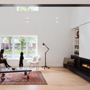 Offenes Nordisches Wohnzimmer mit weißer Wandfarbe, Kamin, Kaminumrandung aus Metall und verstecktem TV in Toronto