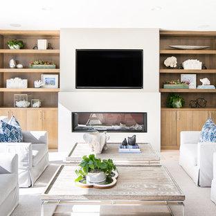 サンディエゴのビーチスタイルのおしゃれなファミリールーム (横長型暖炉、壁掛け型テレビ、白い壁) の写真