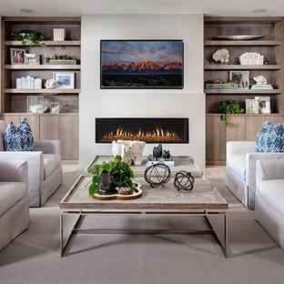 サンディエゴの大きいビーチスタイルのおしゃれなファミリールーム (横長型暖炉、漆喰の暖炉まわり、壁掛け型テレビ、白い壁、カーペット敷き) の写真