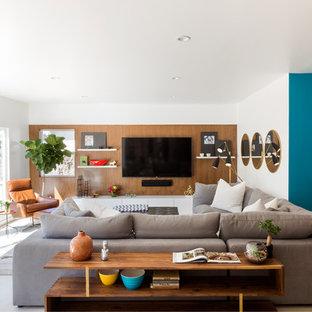 Ejemplo de sala de estar abierta, retro, de tamaño medio, con paredes blancas, suelo de piedra caliza, televisor colgado en la pared y suelo beige