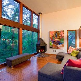 Modernes Wohnzimmer mit beiger Wandfarbe, braunem Holzboden, Eckkamin und Eck-TV in Austin