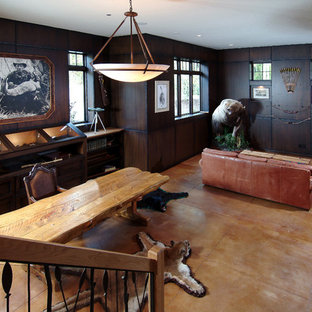 This is an example of a large traditional enclosed family room in Grand Rapids with brown walls and concrete floors.