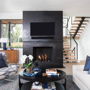 オースティンの中くらいのコンテンポラリースタイルのおしゃれなオープンリビング (淡色無垢フローリング、標準型暖炉、コンクリートの暖炉まわり、壁掛け型テレビ、ベージュの床、黒い壁) の写真