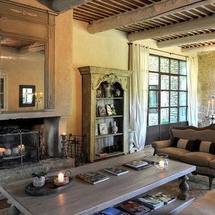 Ejemplo de sala de estar abierta, campestre, extra grande, sin televisor, con paredes multicolor, suelo de piedra caliza, chimenea tradicional, marco de chimenea de piedra y suelo beige