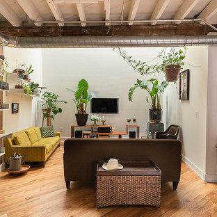 Foto de sala de estar abierta, industrial, con paredes blancas, suelo de madera en tonos medios y televisor colgado en la pared