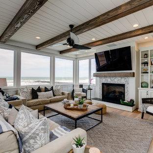 Cette image montre une salle de séjour marine de taille moyenne et ouverte avec un mur blanc, une cheminée standard, un manteau de cheminée en carrelage, un téléviseur fixé au mur, un sol beige et un sol en bois clair.