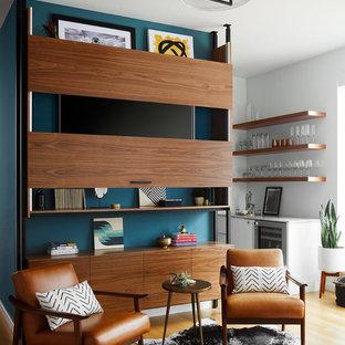 Modelo de sala de estar abierta, contemporánea, grande, sin chimenea, con suelo de madera clara y televisor retractable