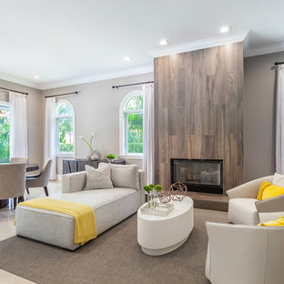 Example of a large trendy open concept marble floor and beige floor game room design in Miami with gray walls, a wood stove, a tile fireplace and a wall-mounted tv