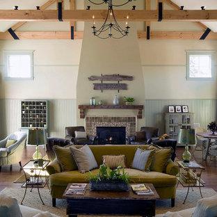 Modelo de sala de estar abierta, rural, grande, sin televisor, con chimenea tradicional, marco de chimenea de baldosas y/o azulejos, paredes verdes y suelo de madera en tonos medios