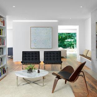 トロントのコンテンポラリースタイルのおしゃれなファミリールーム (ライブラリー、白い壁、無垢フローリング、標準型暖炉、コンクリートの暖炉まわり) の写真