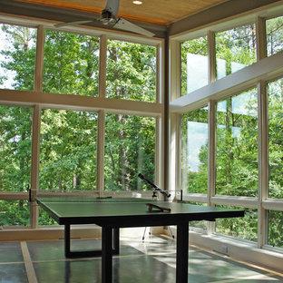 Foto di un soggiorno design aperto con sala giochi, pareti grigie e pavimento in cemento