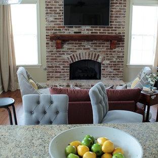 Foto de sala de estar abierta, pequeña, con paredes beige, suelo de madera clara, chimenea tradicional, marco de chimenea de ladrillo, televisor colgado en la pared y suelo marrón
