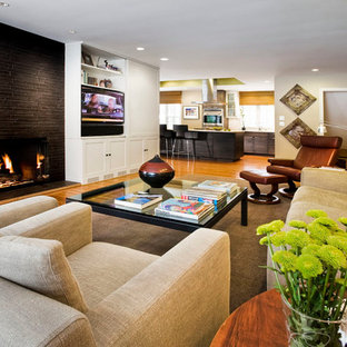 Trendy open concept medium tone wood floor family room photo in Other with beige walls, a standard fireplace and a media wall