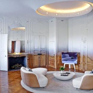 Cette image montre une grande salle de séjour bohème fermée avec un mur multicolore, un sol en bois brun, une cheminée standard, un manteau de cheminée en pierre et un téléviseur indépendant.