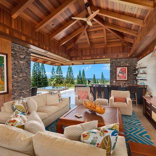 ハワイの大きいトロピカルスタイルのおしゃれなファミリールーム (ホームバー、ライムストーンの床、グレーの床、茶色い壁、暖炉なし、壁掛け型テレビ) の写真