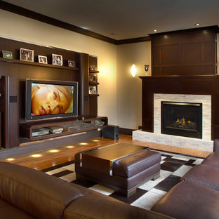 Inspiration for a contemporary medium tone wood floor family room remodel in Los Angeles with beige walls, a standard fireplace and a media wall