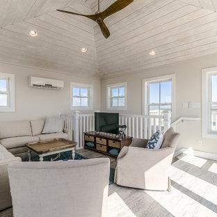 ヒューストンの中サイズのビーチスタイルのおしゃれなファミリールーム (ゲームルーム、グレーの壁、セラミックタイルの床、据え置き型テレビ、ベージュの床) の写真