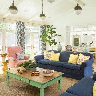 Modelo de sala de estar abierta, de estilo de casa de campo, extra grande, con paredes blancas, suelo de madera clara, televisor colgado en la pared y suelo marrón