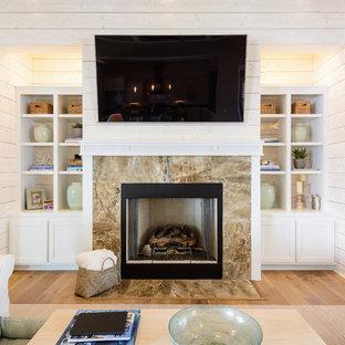 ジャクソンビルの大きいビーチスタイルのおしゃれなファミリールーム (ベージュの壁、淡色無垢フローリング、標準型暖炉、石材の暖炉まわり、壁掛け型テレビ) の写真