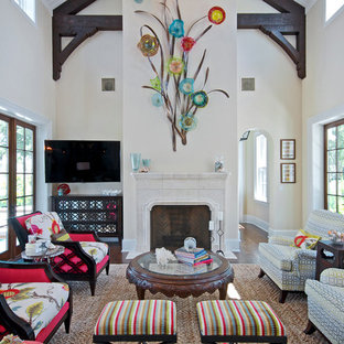Immagine di un soggiorno tropicale chiuso con pareti bianche, camino classico, cornice del camino in pietra e porta TV ad angolo