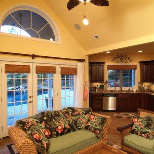 Idée de décoration pour une salle de séjour ethnique ouverte et de taille moyenne avec béton au sol et un mur jaune.