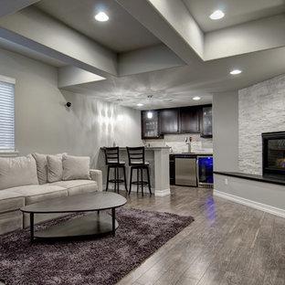 Imagen de sala de estar con barra de bar abierta, actual, grande, con paredes grises, suelo de madera oscura, chimenea tradicional, marco de chimenea de piedra, televisor colgado en la pared y suelo marrón