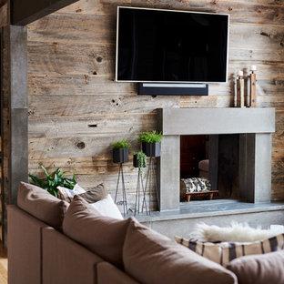 デンバーの中サイズのコンテンポラリースタイルのおしゃれなファミリールーム (茶色い壁、淡色無垢フローリング、両方向型暖炉、コンクリートの暖炉まわり、壁掛け型テレビ、茶色い床) の写真