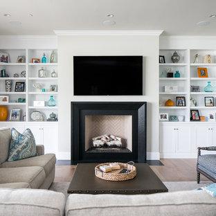 Ejemplo de sala de estar clásica renovada con suelo de madera clara, chimenea tradicional, televisor colgado en la pared y marco de chimenea de yeso