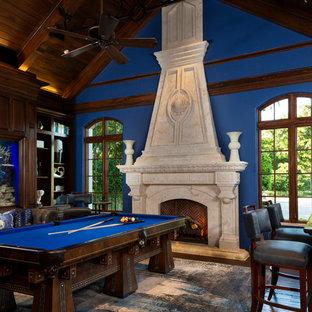 マイアミのトランジショナルスタイルのおしゃれなファミリールーム (ゲームルーム、青い壁、無垢フローリング、標準型暖炉、石材の暖炉まわり、茶色い床) の写真