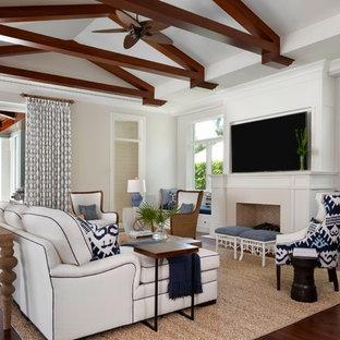 マイアミの大きいトロピカルスタイルのおしゃれなファミリールーム (白い壁、標準型暖炉、壁掛け型テレビ、茶色い床、濃色無垢フローリング) の写真