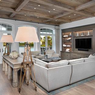 Imagen de sala de estar costera con paredes blancas, suelo de madera clara y pared multimedia
