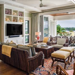 Idée de décoration pour une grande salle de séjour ethnique avec un mur vert, un sol en bois brun et un téléviseur encastré.