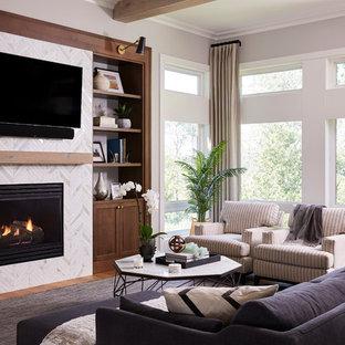 Cette photo montre une grande salle de séjour chic ouverte avec une cheminée standard, un manteau de cheminée en carrelage, un téléviseur fixé au mur, un mur gris et un sol en bois clair.