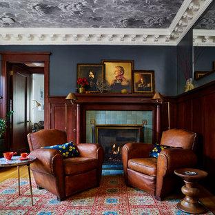 Ejemplo de sala de estar con biblioteca ecléctica, de tamaño medio, con suelo de madera en tonos medios, chimenea tradicional, marco de chimenea de baldosas y/o azulejos y paredes negras